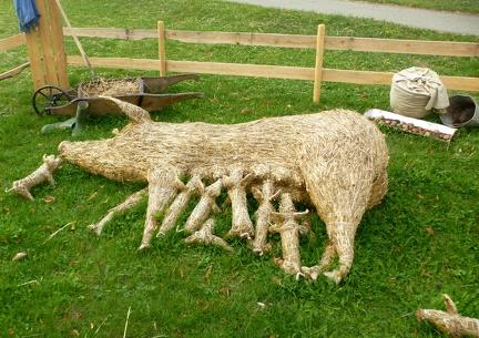 Stillende Sau mit Ferkel -- Der jährliche Strohpark mit Skulpturen aus Stroh in Schwenningen Heuberg im Landkreis Sigmaringen im Naturpark obere Donau in Baden Würtemberg gelegen.